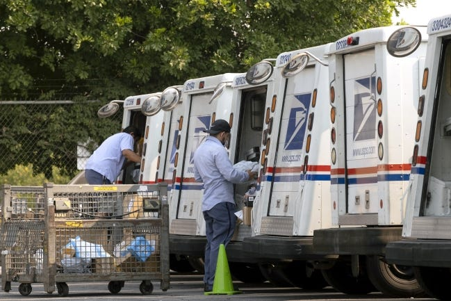 FILE - In this Aug. 20, 2020 file photo, postal workers load their mail delivery vehicles at the Panorama city post office in Los Angeles. The Nov. 3 election will test California's commitment to voting by mail as the nation's most populous state will offer fewer in-person polling places hoping it will convince more people to cast ballots from the safety of their mailboxes during a pandemic. If it doesn't work, the state could see long lines and frustrated voters on Election Day compounded by coronavirus protocols that will make voting in person slower in a year expected to draw a big turnout. (AP Photo/Richard Vogel, File)