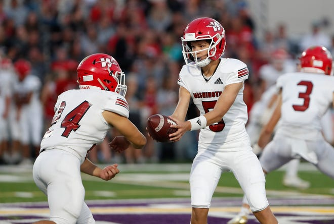 Washington quarterback Jaxon Hendrix hands the ball to running back Chase Allison during Friday's game at Community Christian in Norman. [Alonzo J. Adams/For The Oklahoman]
