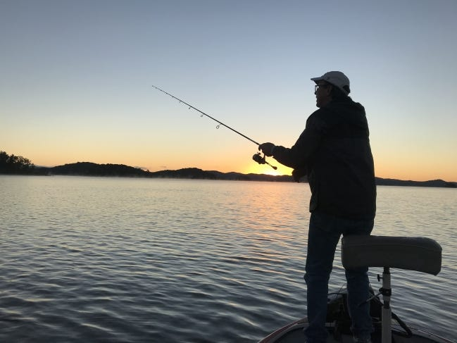 The sun rises on Broken Bow Lake as Mike Newman begins a morning of bass fishing. [LINDA LYNN/THE OKLAHOMAN]