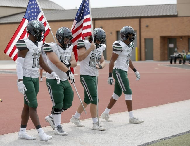 Edmond Santa Fe enters the field with flags for a military appreciation ceremony before a game against Westmoore on Oct. 3 at Moore Stadium. [Sarah Phipps/The Oklahoman]
