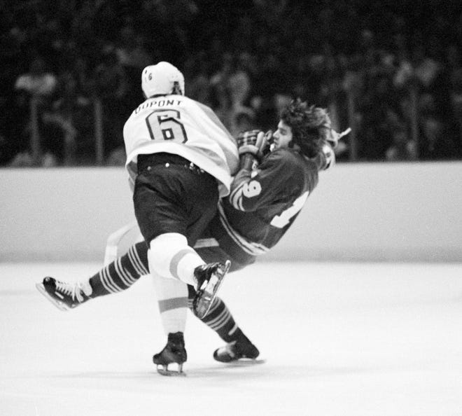 Morris Titanic (19) of the Buffalo Sabres loses his balance as he collides with Andre Dupont (6) of the Flyers in the first period of game in Philadelphia on Saturday, Feb. 1, 1975. (AP Photo/Rusty Kennedy)