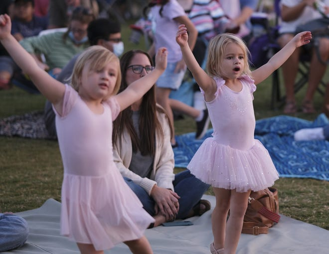 ABOVE: Two young ballerinas mimic moves during OKC Ballet Under the Stars at Scissortail Park on Friday.  LEFT: Ballerinas perform during OKC Ballet Under the Stars at Scissortail Park on the Love's Travel Stops Stage on Friday. [Doug Hoke/The Oklahoman]