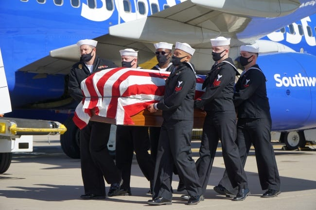 Members of the Wichita Navy Reserve carry the casket of Rex E. Wise toward a hearse at the Dwight D. Eisenhower National Airport in Wichita on Tuesday. [Jordan Green/The Blackwell Journal-Tribune]