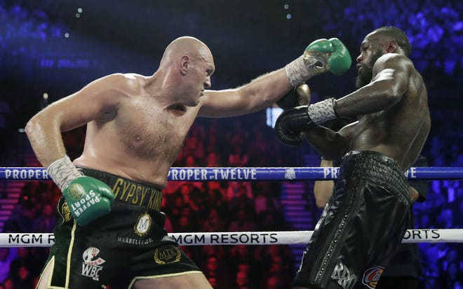 Tyson Fury, left, of England, fights Deontay Wilder during a WBC heavyweight championship boxing match in Las Vegas on February 22. Fury is turning his attention to an all-British heavyweight unification bout with Anthony Joshua early next year after ending plans for a third fight with Deontay Wilder. [AP Photo/Isaac Brekken, File]