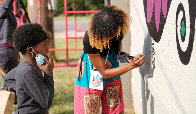 """Oklahoma artist Ebony Inman Dallas, right, works on a mural for """"Celebration of With Love,"""" an Eastside Public Art Project where six local Black artists painted murals on the side of The Market building at 1708 NE 23. The event, which included music and food, was on Saturday, October 3, 2020. [Doug Hoke/The Oklahoman Archives]"""