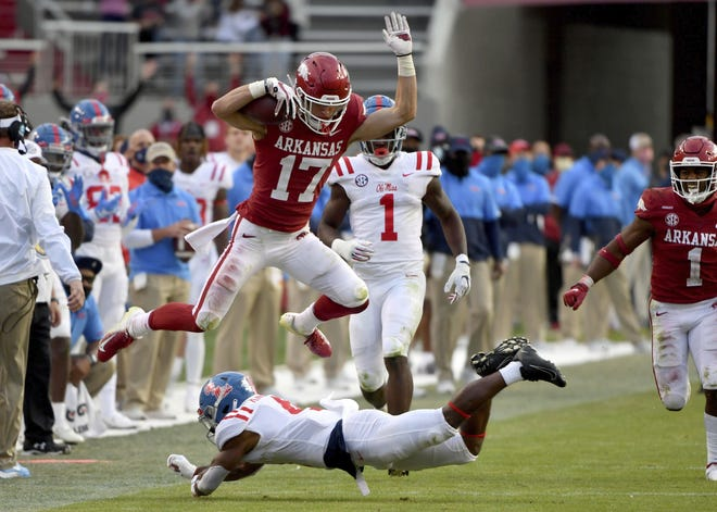 Arkansas defensive back Hudson Clark (17) leaps over Mississippi running back Tylan Knight (4) as he returns an interception during the second half of a 33-21 win Saturday in Fayetteville, Ark. [Michael Woods/the associated press]