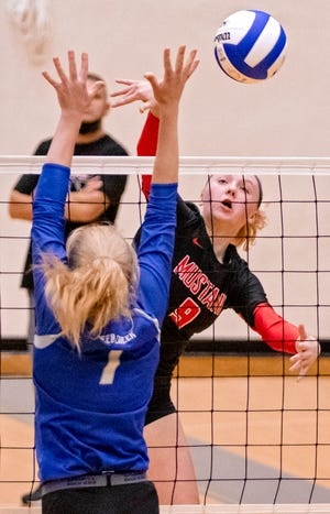 Mustang's Madelyn Booth (9) hits the ball against Deer Creek's Cami Turner (1) during the high school state championship volleyball quarterfinals of the at Choctaw High School in Choctaw, Okla. on Monday, Oct. 19, 2020. [Chris Landsberger/The Oklahoman]