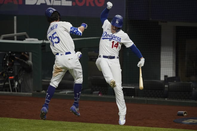 Dodgers slugger Cody Bellinger celebrates his home run with Kike Hernandez against the Atlanta Braves during the seventh inning in Game 7. [AP Photo/Tony Gutierrez]