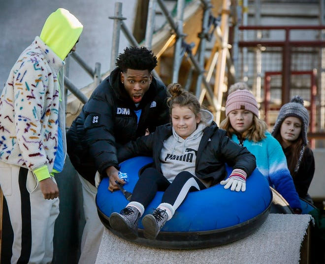 Oklahoma City Thunder player Shai Gilgeous-Alexander helps a rider get started down a slope next to Darius Bazley, left, during a visit by Thunder basketball players to the LifeShare WinterFest at Chickasaw Bricktown Ballpark in Oklahoma City, Monday, Dec. 30, 2019. [The Oklahoman Archives]