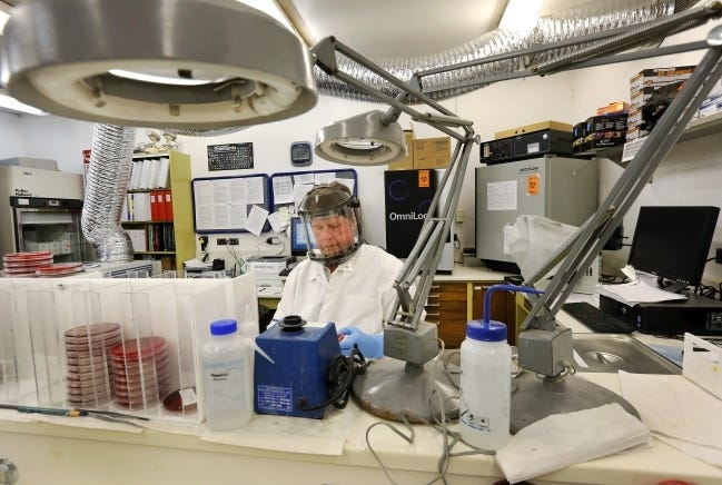 An employee is shown at his work station in the Oklahoma public health laboratory in this 2014 photo. [The Oklahoman Archives]