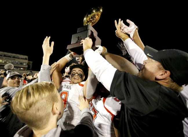 Carl Albert's Reise Collier holds the Class 5A state football championship trophy last December at Wantland Stadium in Edmond. [Sarah Phipps/The Oklahoman]