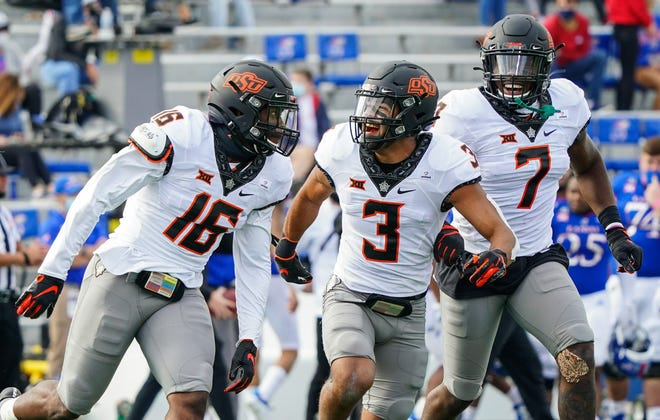 Oklahoma State's Devin Harper (16) is congratulated by Tre Sterling (3) and Amen Ogbongbemiga (7) after intercepting a pass in a 47-7 win at Kansas on Oct. 3. At 3-0 overall, the Cowboys are the only undefeated team in the Big 12. [Jay Biggerstaff/USA TODAY Sports]