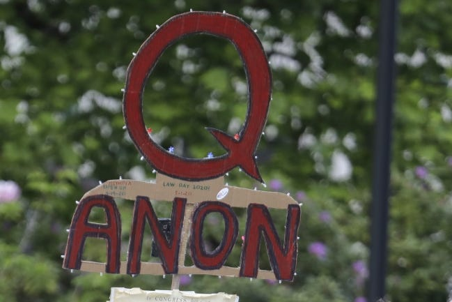 FILE - In this May 14, 2020, file photo, a person carries a sign supporting QAnon at a protest rally in Olympia, Wash. Facebook said Tuesday, Oct. 6, 2020, that it will remove Facebook pages, groups and Instagram accounts for þÄúrepresenting QAnon.þÄù (AP Photo/Ted S. Warren, File)