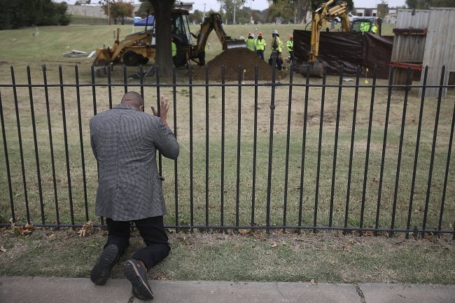 Rev. Robert Turner, with Vernon A.M.E Church, prays Tuesday as crews work on a second test excavation and core sampling in the search for remains at Oaklawn Cemetery in Tulsa from the 1921 Tulsa Race Massacre. (Mike Simons/Tulsa World via AP)