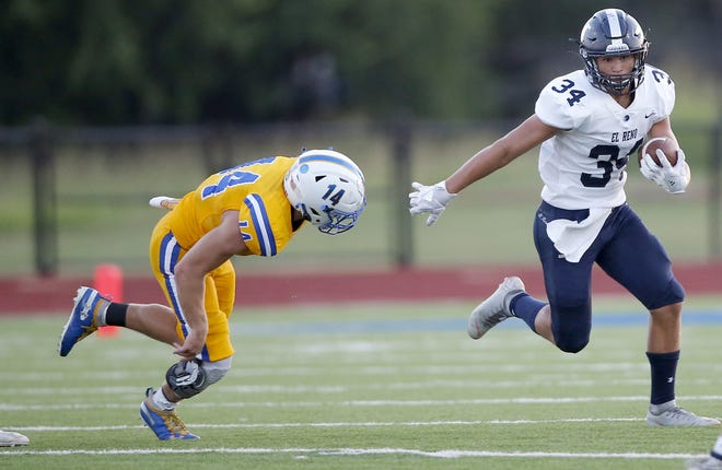 El Reno's Micheal Devereaux (right) rushes away from Piedmont's Joey Mars during a game Sept. 4 in Piedmont. [Sarah Phipps/The Oklahoman]