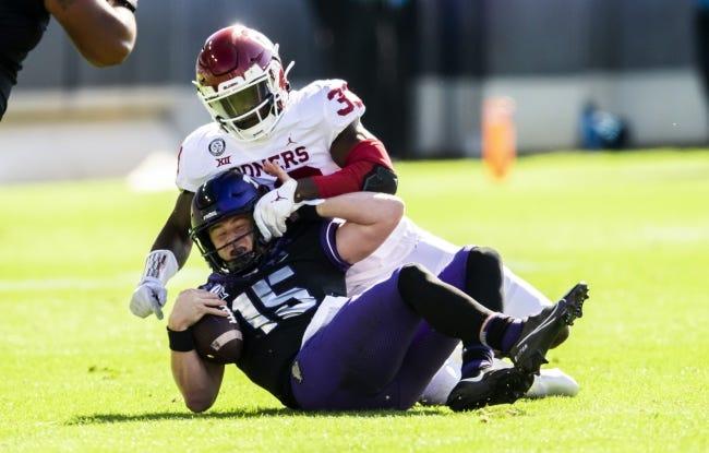 Oklahoma defensive end Marcus Stripling (33) sacks TCU quarterback Max Duggan (15) during the first half Saturday. [AP Photo/Brandon Wade]