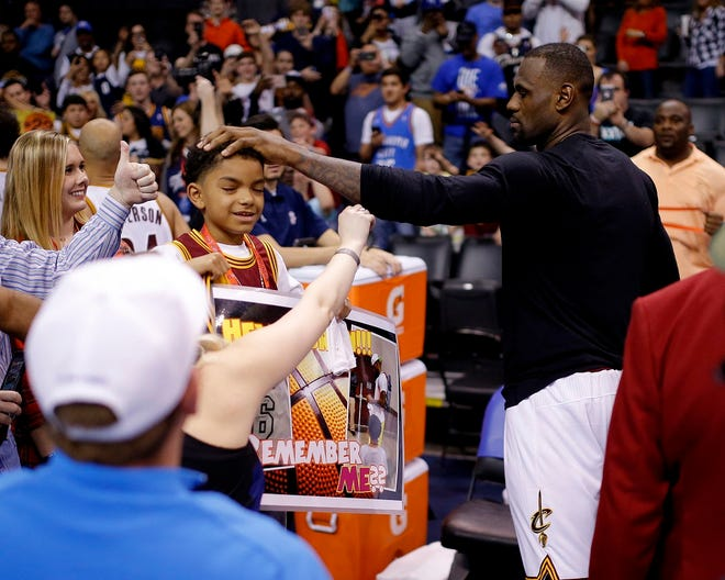 Cleveland's LeBron James pats Donte Jones, 8, of Arkansas after an NBA basketball game between the Oklahoma City Thunder and the Cleveland Cavaliers at Chesapeake Energy Arena in Oklahoma City, Sunday, Feb. 21, 2016. [Bryan Terry/The Oklahoman Archives]