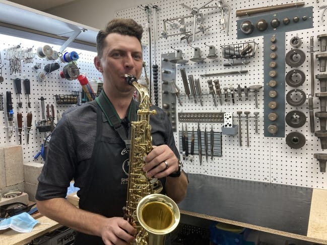 Repair technician Colter Weatherholtz tries out an alto sax brought in to Larsen Music for repairs. [KIMBERLY BURK]