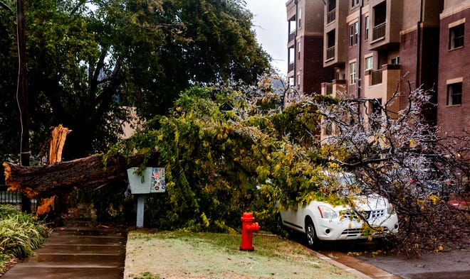A broken tree covers a car in Oklahoma City, Okla. on Tuesday, Oct. 27, 2020, after a winter blast covered the state with ice. [Chris Landsberger/The Oklahoman]