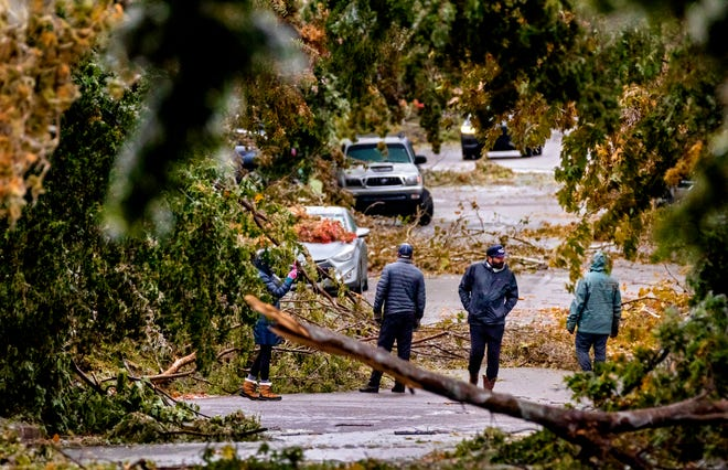 Neighbors in Heritage Hills survey the damage as debris from broken ice covered trees litter the road on NW 14th St. in Oklahoma City, Okla. on Tuesday, Oct. 27, 2020, after a winter blast covered the state with ice.[Chris Landsberger/The Oklahoman]