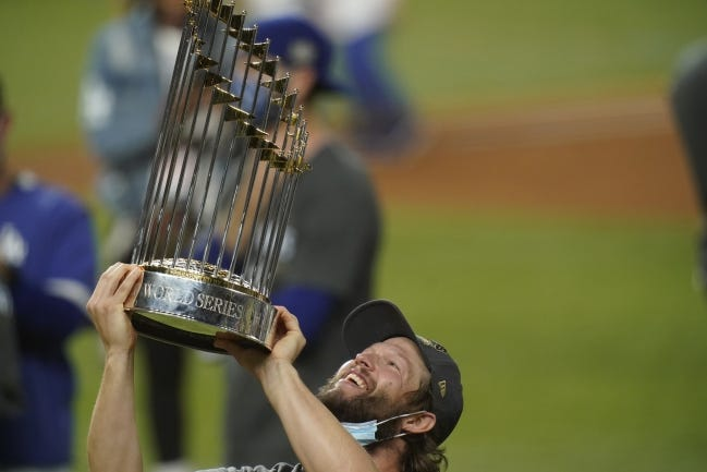 Los Angeles Dodgers pitcher Clayton Kershaw celebrates with the trophy after defeating the Tampa Bay Rays 3-1 on Tuesday to win the World Series. [AP Photo/Eric Gay]