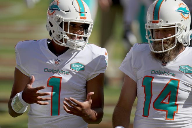 Miami Dolphins quarterback Tua Tagovailoa (1) and quarterback Ryan Fitzpatrick (14) talk on the field before an NFL football game against the San Francisco 49ers, Sunday, Oct. 11, 2020, in Santa Clara, Calif. Miami Dolphins coach Brian Flores says he regrets that his players found out about the team's switch to quarterback Tua Tagovailoa through social media rather than from him. And Flores says the decision to bench popular veteran Ryan Fitzpatrick was difficult.(AP Photo/Scot Tucker)