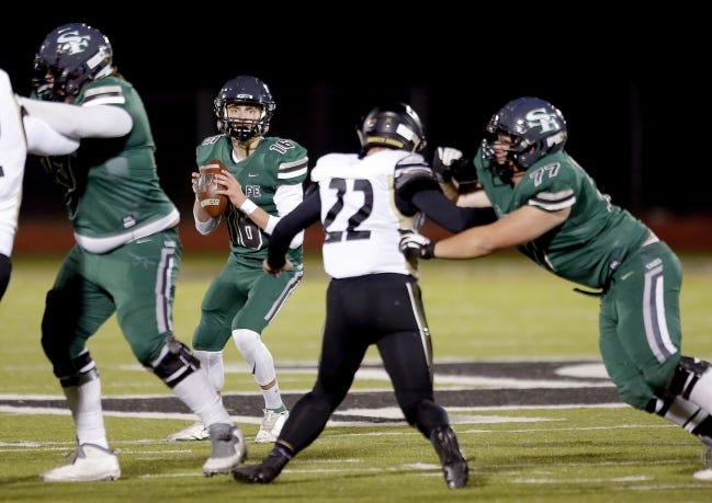 Edmond Santa Fe quarterback Scott Pfieffer, seen here during a regular-season game against Broken Arrow, has thrown for more than 2,200 yards this season. His dad, Roger, is the Wolves' quarterback coach, and together, they've helped lead Edmond Santa Fe back to the state finals for the first time since 2003. [SARAH PHIPPS/THE OKLAHOMAN]