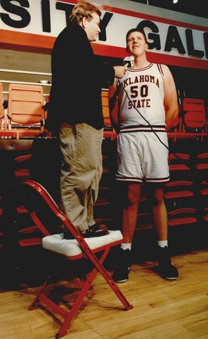 """Sportscaster Mick Cornett stands on a padded folding chair to interview """"Big Country,"""" Oklahoma State University's center Bryant Reeves in October 1992 during the Cowboys' media day. Reeves went on to play for the NBA Vancouver Grizzlies team from 1995 to 2001. Cornett became the 35th Oklahoma City mayor, serving from 2004 to 2018. [STEVE GOOCH/THE OKLAHOMAN ARCHIVES]"""