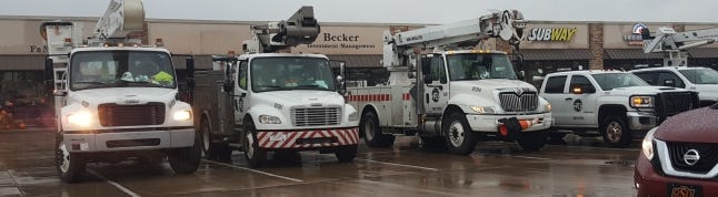 Trucks from a company that is helping Oklahoma Gas and Electric restore power in central Oklahoma are staged at a strip mall in southern Logan County early Thursday. [JACK MONEY/THE OKLAHOMAN]