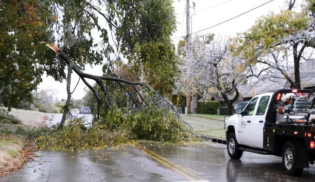 An Edmond Field Services truck blocks Rankin at 15th St. where a large branch fell and blocked the road during an ice storm that hit the Oklahoma City metro area Tuesday. [Doug Hoke/The Oklahoman]