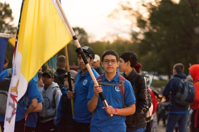"""A youth holds a flag during the """"Road to Restoration"""" pilgrimage. [MissChelle Photography]"""