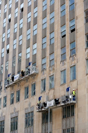 Work has moved to the north exterior of the First National Center as crews scale the 33-story tower securing limestone panels that were in danger of falling off as some did at the start of the $283 million redevelopment. [DOUG HOKE/THE OKLAHOMAN]