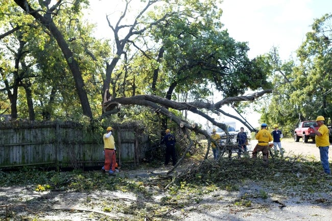 In this Oct. 30 photo, a group from the Oklahoma Baptists Disaster Relief team works on tree limb removal in Bethany. [Doug Hoke/The Oklahoman]