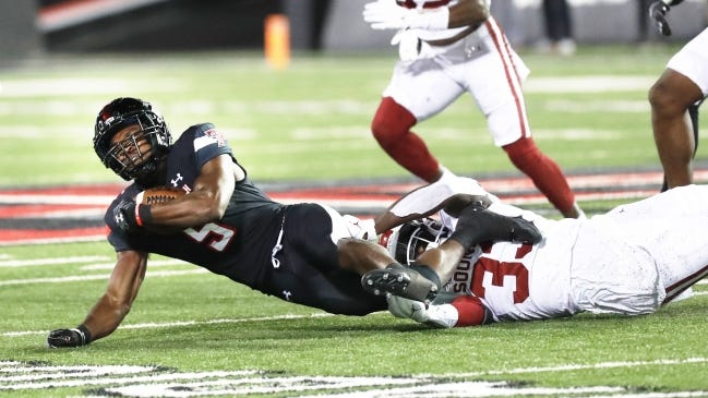 Texas Tech running back Chadarius Townsend is tackled by Oklahoma defensive end Marcus Stripling during the second half of the Sooners' 62-28 win Saturday in Lubbock, Texas. [AP Photo/Mark Rogers]