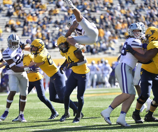 Kansas State defensive back Kiondre Thomas (3) leaps over West Virginia running back Leddie Brown (4) as he attempts to block a pass during Saturday's game in Morgantown, W.Va. [William Wotring/The Dominion-Post via AP]