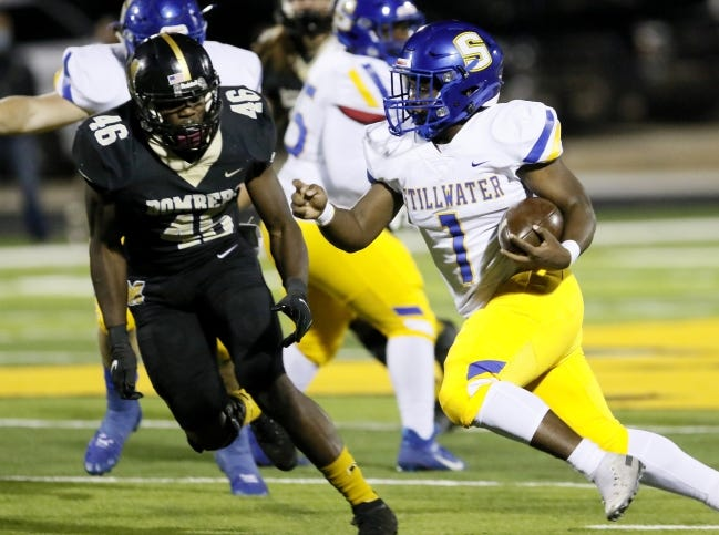Stillwater's Qwontrel Walker looks to get by Midwest City's LeJaylyn Long-Jackson during a 31-10 win last Friday. [Sarah Phipps/The Oklahoman]