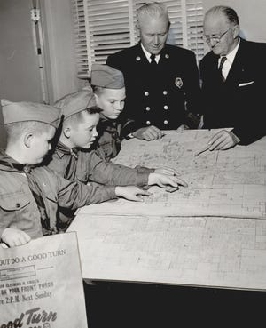 Boy Scouts of the Last Frontier Council look forward to their 'Good Turn' drive in November 1960. About 14,000 Scouts blanketed metro area neighborhoods, leaving paper sacks for residents to fill with used clothing for Goodwill Industries. The Scouts returned to the neighborhoods to pick up the donations, but some fire stations also were used as drop-off locations. Pictured at left is Oklahoma City Fire Chief Graves Haskell. At right is Tom Garrett, chairman of that year's 'Good Turn' clothing drive. [JOE MILLER/THE OKLAHOMAN ARCHIVES]