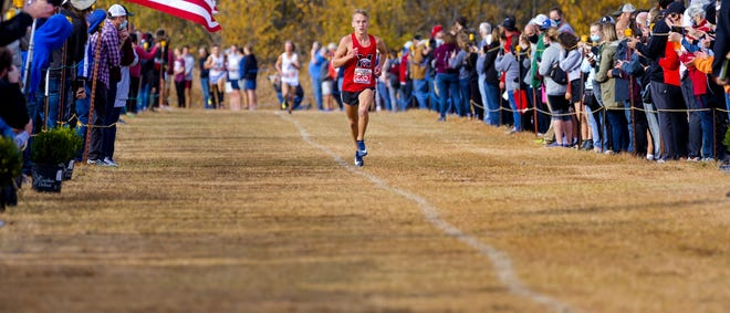 Mustang's Gabe Simonsen (235) runs alone to the finish line to take the state title during the 6A boys cross country state championships at Edmond Santa Fe High School on Wednesday. [Chris Landsberger/The Oklahoman]