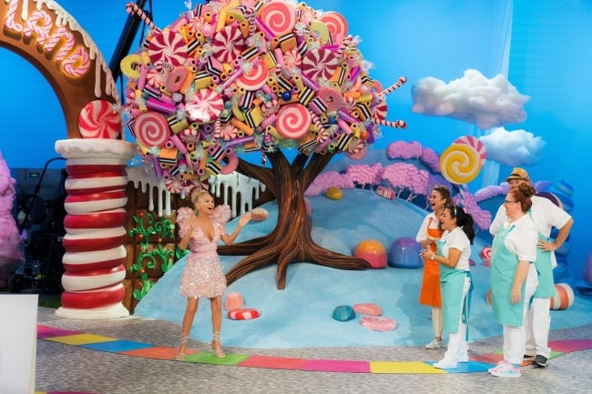 """From left, """"Candy Land"""" host Kristin Chenoweth speakes with contestants Cinthya Romriell, Eric Kroeker, Brittani Diehl and Reva Alexander-Hawk on an episode of the first season of the new Food Network competition series based on the classic board game. """"Candy Land"""" premieres at 8 p.m. Nov. 15. [Food Network photo]"""