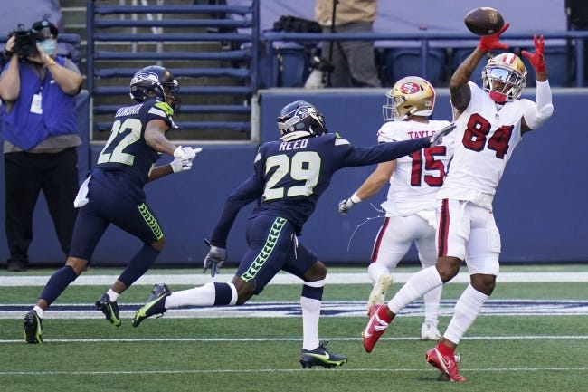 San Francisco 49ers wide receiver Kendrick Bourne (84) makes a catch in front of Seattle Seahawks cornerback D.J. Reed (29) during last Sunday's game in Seattle. [AP Photo/Elaine Thompson]