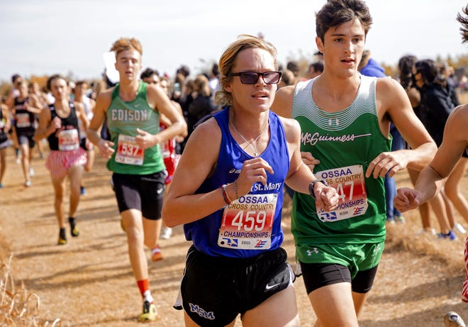 Mount St. Mary's Jake Hunsucker (459) and Bishop McGuinness' Luke Chansolme (347) compete during the 5A boys cross country state championships at Edmond Santa Fe on Wednesday. [Chris Landsberger/The Oklahoman]