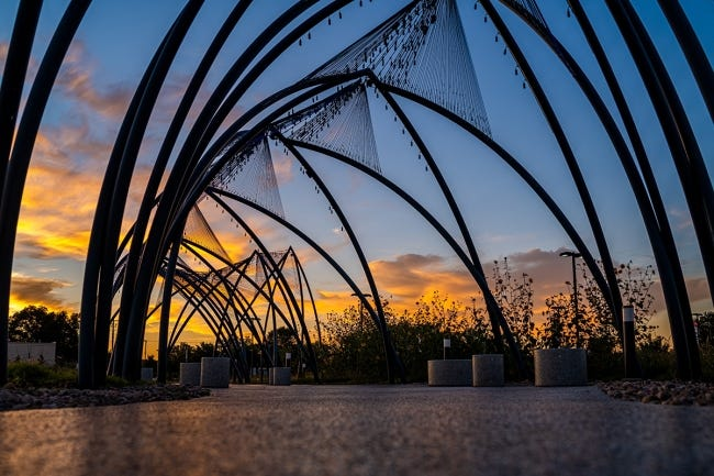 """Enid artist Romy Owens' large-scale public artwork """"Under Her Wing Was the Universe"""" is seen at sunset. [Visit Enid photo]"""