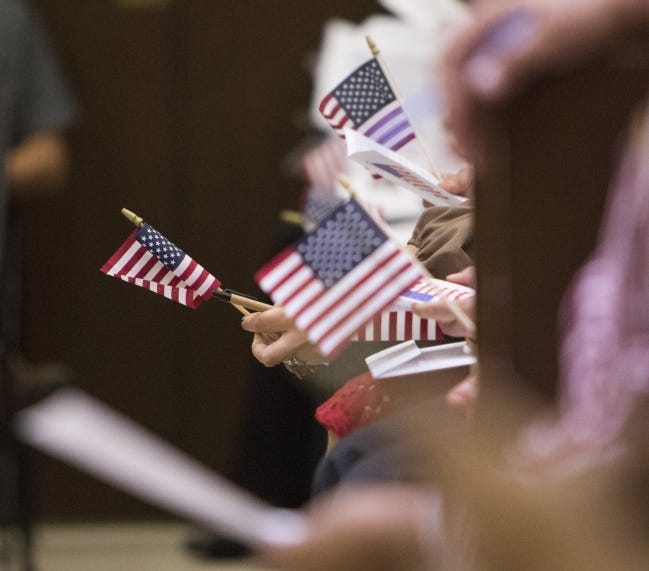 People wave American flags while waiting for a naturalization ceremony at the federal courthouse in Oklahoma City on June 30, 2017. [The Oklahoman Archives]