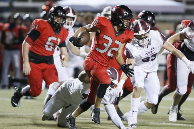 Westmoore's Keshawn Oliver carries the ball during Thursday's game between Westmoore and Jenks in Moore. Jenks won 49-21. [Bryan Terry/The Oklahoman]