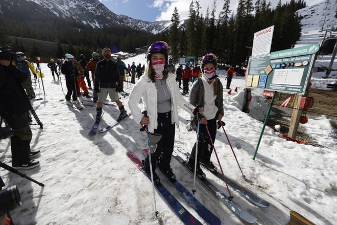 In this May 27 photo, skiers wear face coverings as they wait to board a lift at the reopening of Arapahoe Basin Ski Resort, which closed in mid-March to help in the effort to stop the spread of the new coronavirus in Keystone, Colo. Winter sports enthusiasts will encounter restrictions at resorts in the season ahead to accommodate COVID rules. [AP Photo/David Zalubowski, File]