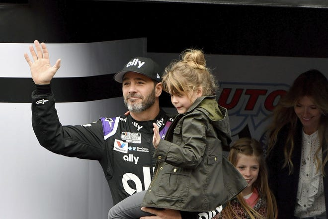 Seven-time NASCAR Cup Series champion Jimmie Johnson is introduced to the crowd March 1 as he carries his youngest daughter Lydia as his oldest daughter Genevieve and wife Chandra follow prior to a March 1 race in Fontana, Calif. [AP Photo/Will Lester, File]
