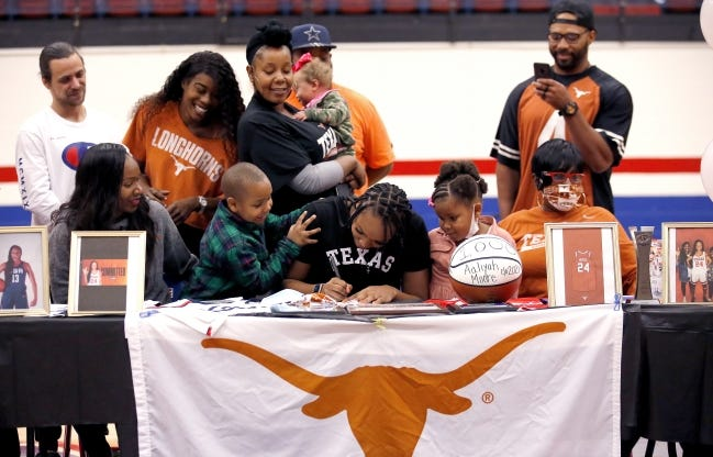 Aaliyah Moore signs with Texas during a signing day ceremony at Moore High School on Wednesday. [Sarah Phipps/The Oklahoman]
