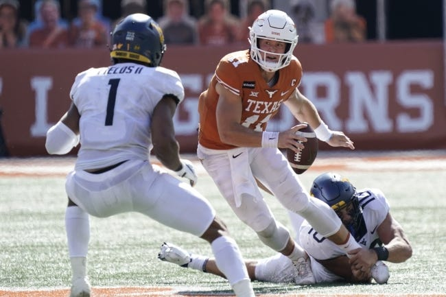 Texas' Sam Ehlinger (11) scrambles against West Virginia's Dylan Tonkery (10) and Tony Fields II (1) during the first half of a game in Austin, Texas last Saturday. [AP Photo/Chuck Burton]
