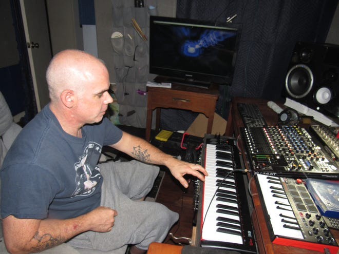 Trent Scoggins works on some music with the keyboard and soundboard he set up at his home. [Cathy Spaulding/Muskogee Phoenix ]
