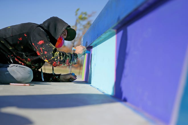 Muralist Dylan Bradway paints a mural on the vertical surfaces of the skate park at Stars and Stripes Park in Oklahoma City. [Bryan Terry photos/The Oklahoman]